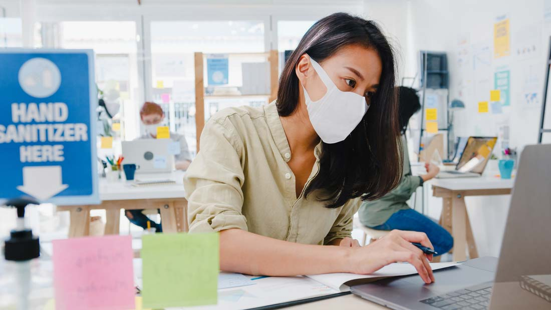 Woman wearing mask while working on laptop
